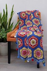 Blue crochet blanket thrown over chair
