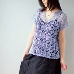 Woman wearing lilac crochet lace tunic over black dress