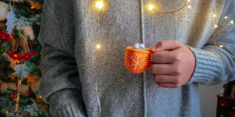Person holding crocheted mug with crocheted hot chocolate in front of christmas tree