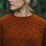 Andrea Mowry wearing burnt orange wool and honey design sweater
