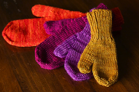4 different sized mittens in various colors